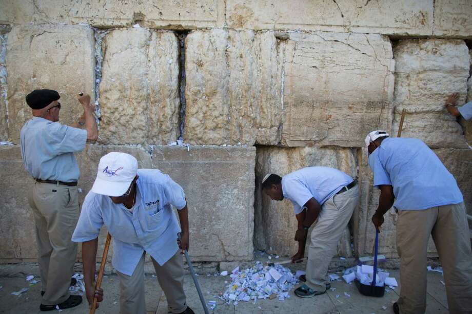 Western Wall employees remove messages and prayers written by thousands of people addressed to God from the cracks in the Western Wall on August 25, 2013 in Jerusalem, Israel. All the notes once collected will be buried in a special place at the Mount of Olives. Photo: Uriel Sinai, Getty Images / 2013 Getty Images