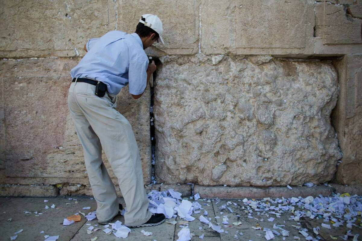Western Wall employees remove messages and prayers written by thousands of people addressed to God from the cracks in the Western Wall on August 25, 2013 in Jerusalem, Israel. All the notes once collected will be buried in a special place at the Mount of Olives.