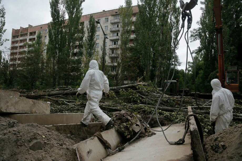 Workers patrol the dead town of Prypyat three kilometers from the Chernobyl nuclear power plant, as dismantling work continues at the scene of the world's worst nuclear accident, in Ukraine, on Sunday, Aug. 25, 2013.  The No. 4 reactor at Chernobyl nuclear power plant was the scene of a major explosion in 1986, resulting in the evacuation of the nearby town and the ongoing legacy of protecting against any possible future radiation leaks. Photo: AP