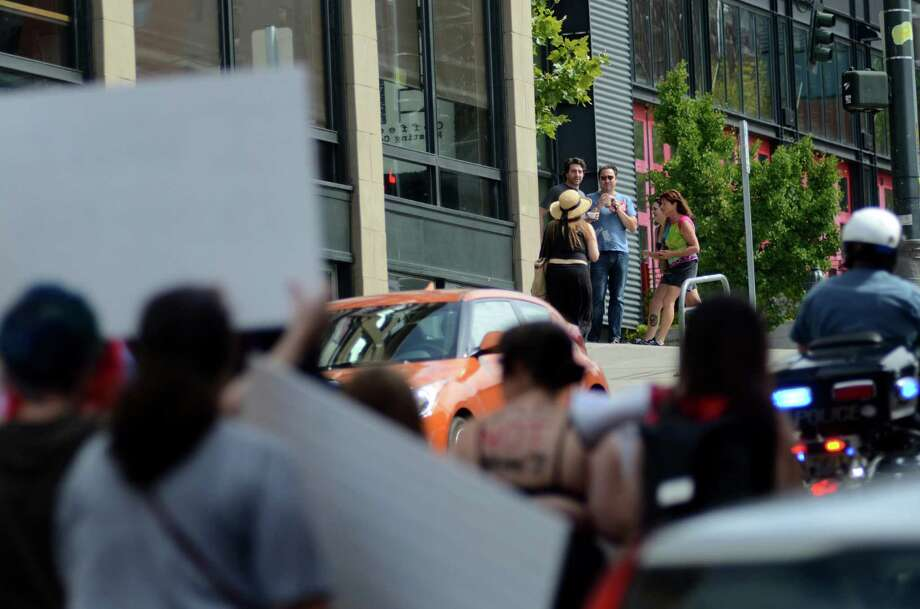 Onlookers watch the protest near 4th Avenue during the annual Slutwalk march Sunday Aug. 25, 2013 in Seattle. Attendees of the walk protested rape culture and gender-based violence in the United States. Photo: SY BEAN, SEATTLEPI.COM / SEATTLEPI.COM