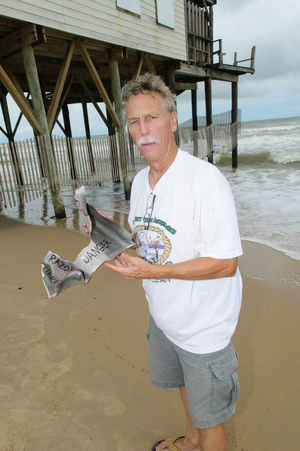 Ellis Pickett chairman of the Surfrider Foundation shows a piece of bulkhead that was found in the water by one of the abandoned homes, in the background.  A rally was held by the Surfrinder Foundation to call attention to two abandoned beach houses on Surfside Beach plus call for their removal. Photo: ©Kim Christensen / ©Kim Christensen