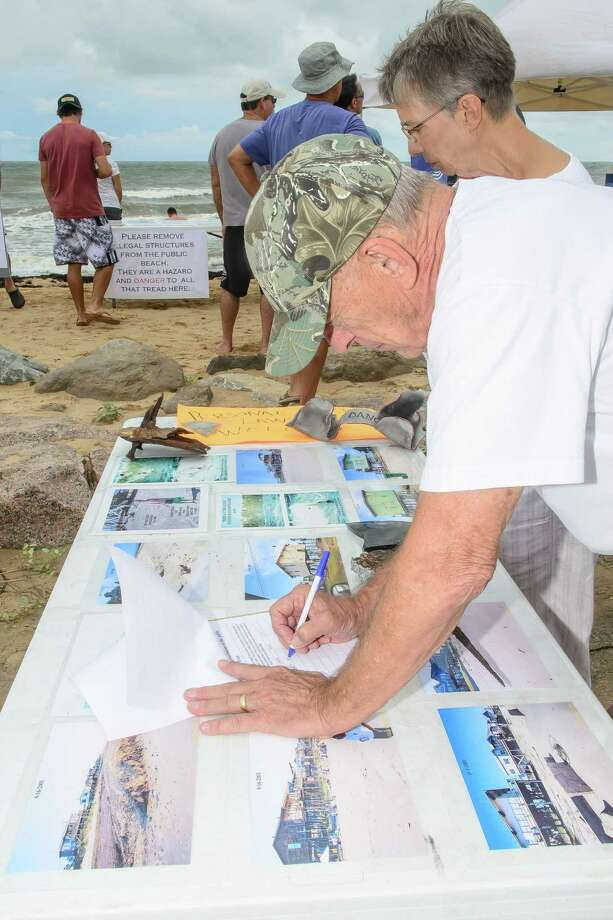 Larry Kelly of West University signs a petition to have two abandon homes on Surfside Beach removed while his wife Edna looks at some images on the table.   A rally was held by the Surfrinder Foundation to call attention to two abandoned beach houses on Surfside Beach plus call for their removal. Photo: ©Kim Christensen / ©Kim Christensen