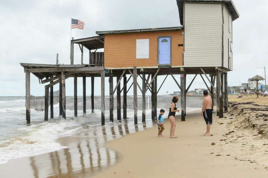 A family looks at one of the two abandon homes that sits along the the water line on Surside Beach.  A rally was held by the Surfrinder Foundation to call attention to two abandoned beach houses on Surfside Beach plus call for their removal, 08/25/13. Photo: ©Kim Christensen / ©Kim Christensen