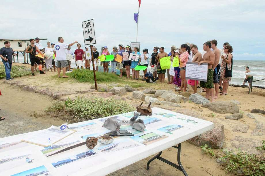 On the table some images of the abandon homes on Surfside Beach plus items found in the water in front of the two abandon homes as Chairman of the Surfrider Foundation, Ellis Pickett speaks in the background