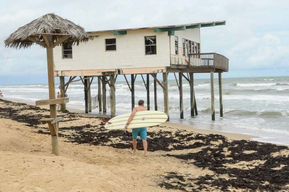 Surfer walks by one of the two abandoned beach houses on Surfside Beach.  A rally was held to call for their removal of the two homes on Surfside Beach, 08/25/13. Photo: ©Kim Christensen / ©Kim Christensen