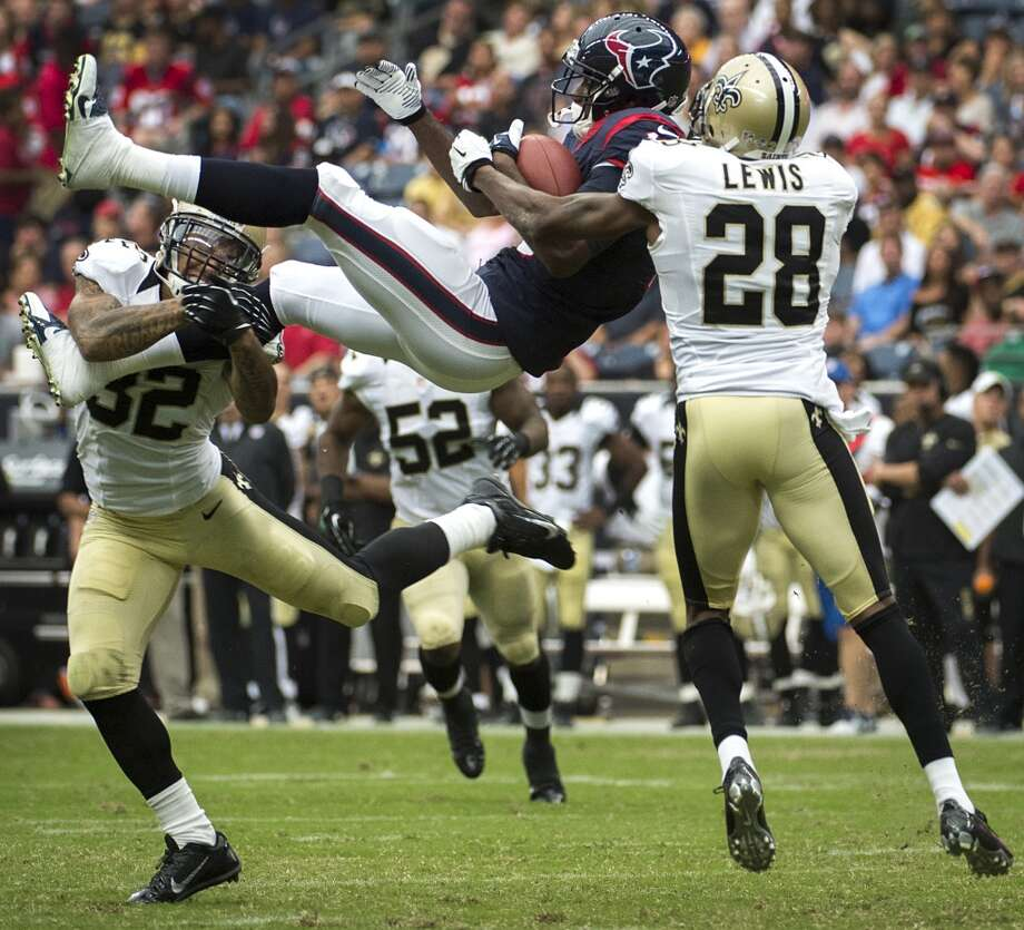 Houston Texans wide receiver Lestar Jean (18) is upended by New Orleans Saints strong safety Kenny Vaccaro (32) and cornerback Keenan Lewis (28) as he makes a catch during the second half of a preseason NFL football game at Reliant Stadium on Sunday, Aug. 25, 2013, in Houston. ( Smiley N. Pool / Houston Chronicle ) Photo: Smiley N. Pool, Houston Chronicle