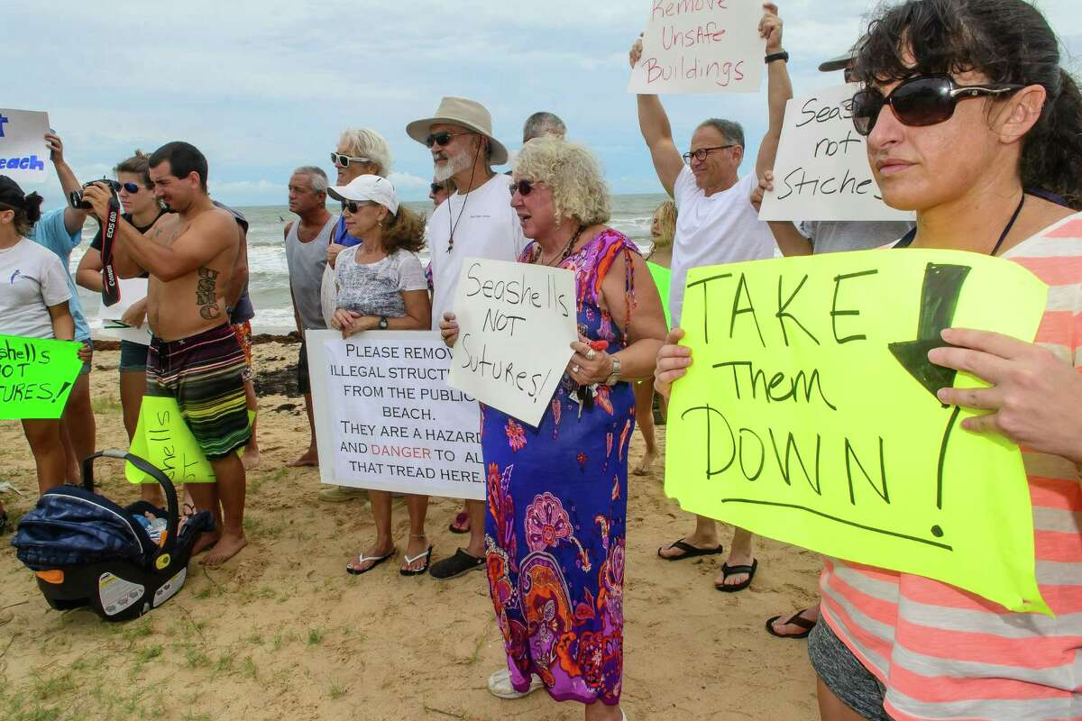 Protesters on Sunday urge that the homes on Surfside Beach be removed. The rally was organized by the conservation group Surfrider Foundation to call attention to a lawsuit that could restrict beach access.