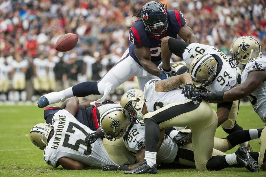 The ball bounces away from Texans running back Ben Tate as he is brought down by the Saints defense during the first half. The play was ruled down by contact. Photo: Smiley N. Pool, Houston Chronicle