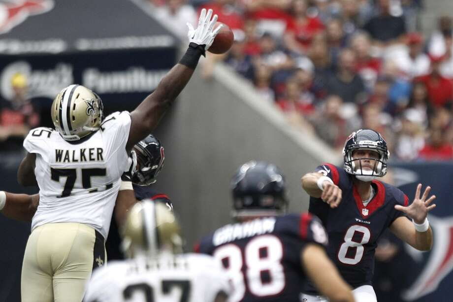 Saints defensive end Tyrunn Walker knocks down a pass by Texans quarterback Matt Schaub. Photo: Brett Coomer, Houston Chronicle