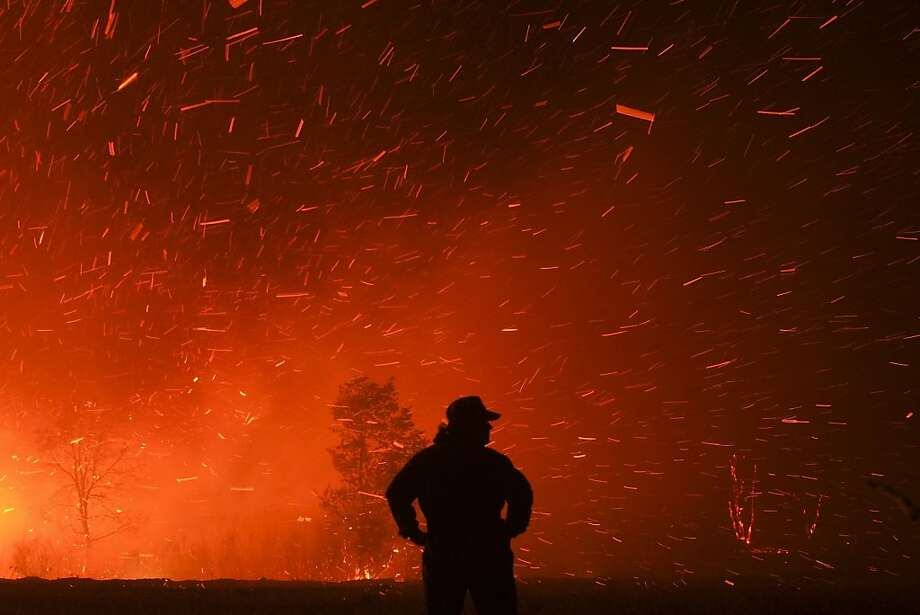 Firebrands scatteras a wildfire burns in the village of Cualedro, near Ourense, 