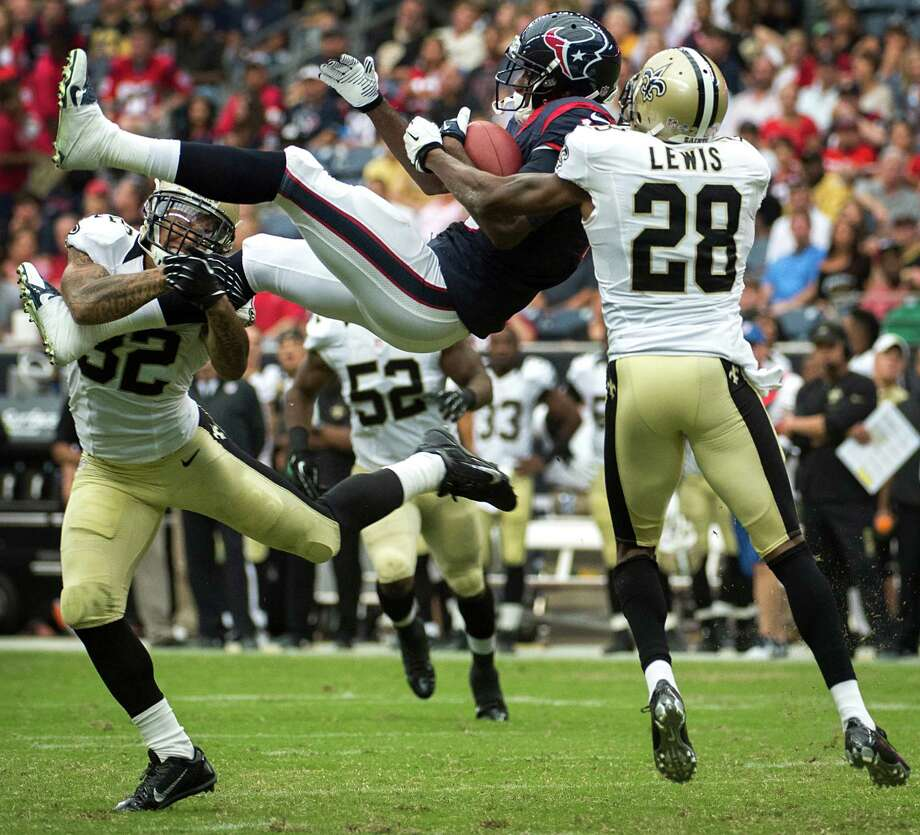 Texans receiver Lestar Jean finds himself in a precarious position between Saints safety Kenny Vaccaro, left, and cornerback Keenan Lewis after a catch. Photo: Smiley N. Pool, Staff / © 2013  Houston Chronicle
