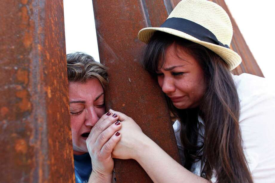 Renata Teodoro, 25 right, holds hands with her mother, Gorete Borges Teodoro, who was deported six years ago from the U.S., through the bars of a border fence in Nogales, Ariz., June 11, 2013. The meeting, between parents and a group of young immigrants who grew up in the U.S. without legal status who call themselves Dreamers, was to highlight their support for a bill in the Senate to overhaul the immigration system. (Samantha Sais/The New York Times) Photo: SAMANTHA SAIS / NYTNS