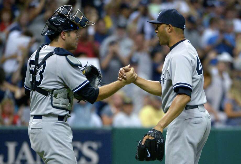 New York Yankees reliever Mariano Rivera, right, is congratulated by catcher Austin Romine after getting the save in a 3-2 victory over the Tampa Bay Rays in a baseball game in St. Petersburg, Fla., Sunday, Aug. 25, 2013. (AP Photo/Phelan M. Ebenhack) ORG XMIT: SPD113 Photo: Phelan M. Ebenhack / FR121174 AP