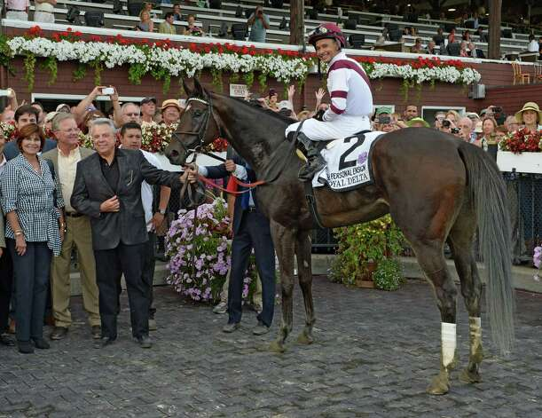 Jockey Mike Smith is all smiles aboard Royal Delta as he is joined in the winner's circle by owner Ben Leon, third from left and trainer Bill Mott, second from left, after winning the 66th running of The Personal Ensign Invitational Aug 25, 2013, at the Saratoga Race Course in Saratoga Springs, N.Y.   (Skip Dickstein/Times Union) Photo: SKIP DICKSTEIN