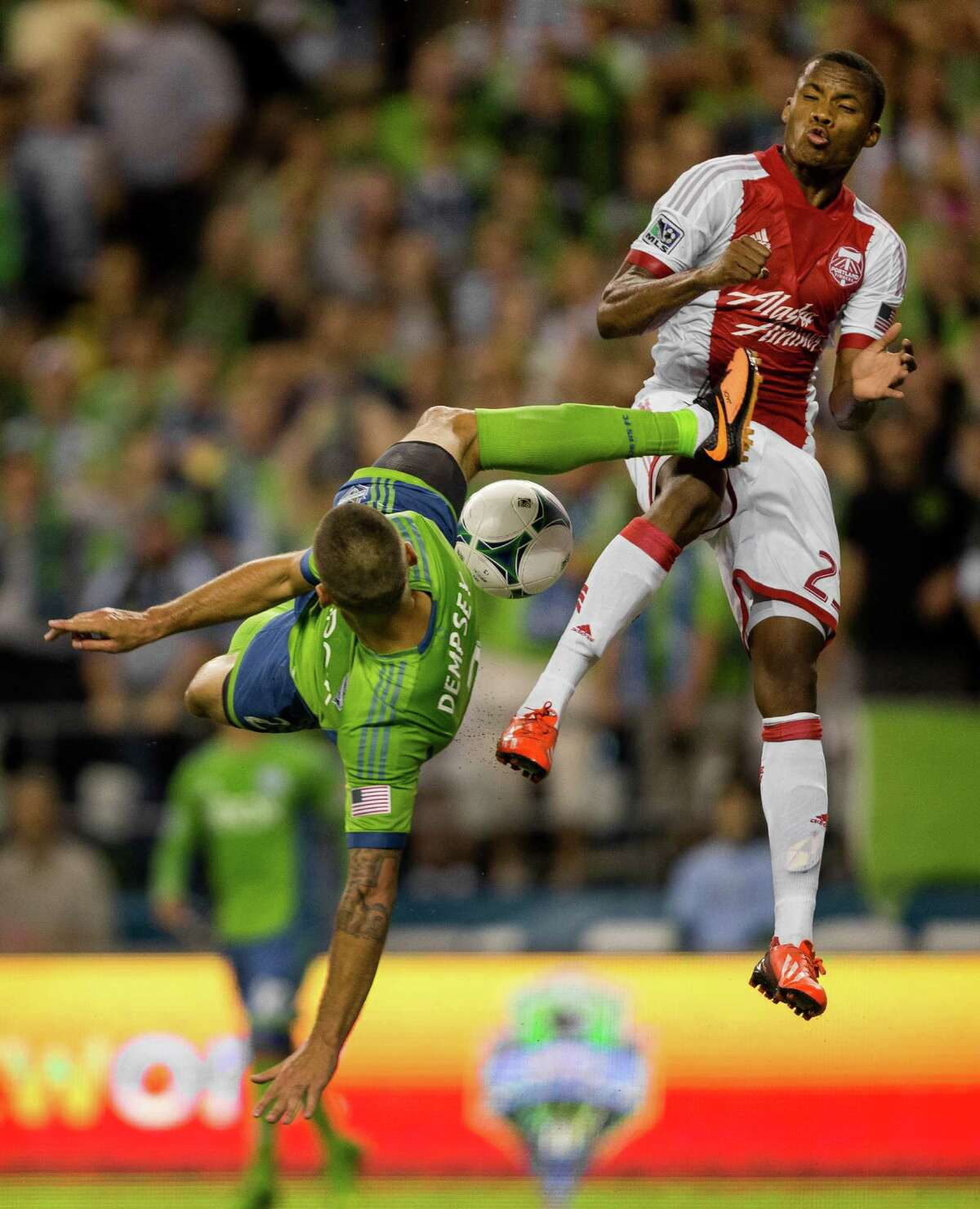 Clint Dempsey, left, goes up for a shot on the Portland Timbers goal with a bicycle kick that nearly struck Alvas Powell, right, during the second half of the Cascadia Cup match Sunday, August 25, 2013, at CenturyLink Field in Seattle. The Sounders beat the Timbers 1-0. The sold-out match marked Clint Dempsey's first home game as a member of the Seattle Sounders FC.