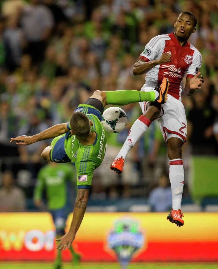 Clint Dempsey, left, goes up for a shot on the Portland Timbers goal with a bicycle kick that nearly struck Alvas Powell, right, during the second half of the Cascadia Cup match Sunday, August 25, 2013, at CenturyLink Field in Seattle. The Sounders beat the Timbers 1-0. The sold-out match marked Clint Dempsey's first home game as a member of the Seattle Sounders FC. Photo: JORDAN STEAD, SEATTLEPI.COM / SEATTLEPI.COM