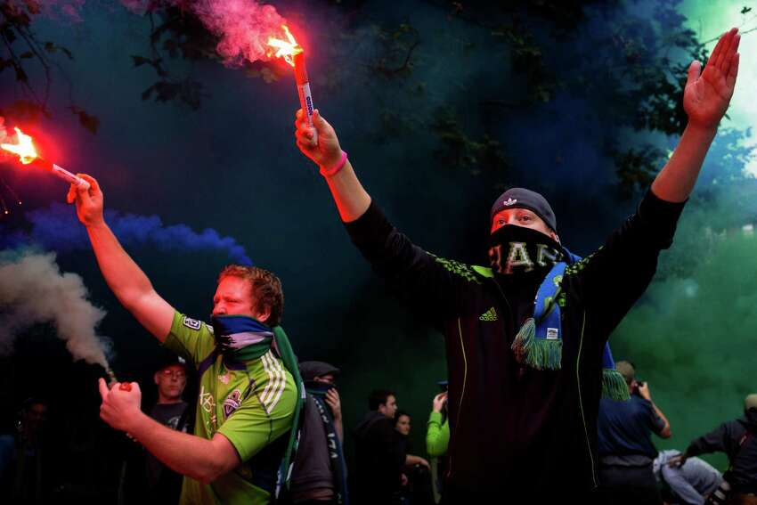 Fans set off flares emitting colored smoke at a Seattle Sounders rally before the Cascadia Cup match against the Portland Timbers Sunday, August 25, 2013, at CenturyLink Field in Seattle. The sold-out match marked Clint Dempsey's first home game as a member of the Seattle Sounders FC.