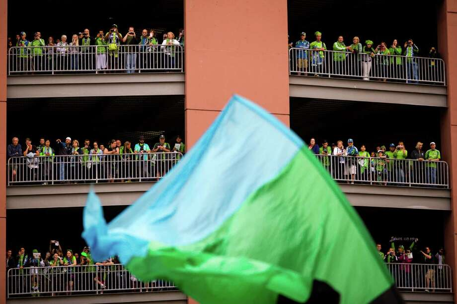 Fans watch a flag-waving march approach CenturyLink Field during a Seattle Sounders rally before the Cascadia Cup match against the Portland Timbers Sunday, August 25, 2013, in Seattle. The sold-out match marked Clint Dempsey's first home game as a member of the Seattle Sounders FC. Photo: JORDAN STEAD, SEATTLEPI.COM / SEATTLEPI.COM