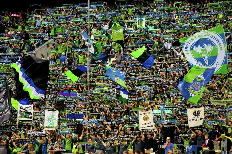 Fans raise their scarves and flags in support before the first half of the Cascadia Cup match Sunday, August 25, 2013, at CenturyLink Field in Seattle. The sold-out match marked Clint Dempsey's first home game as a member of the Seattle Sounders FC. Photo: JORDAN STEAD, SEATTLEPI.COM / SEATTLEPI.COM
