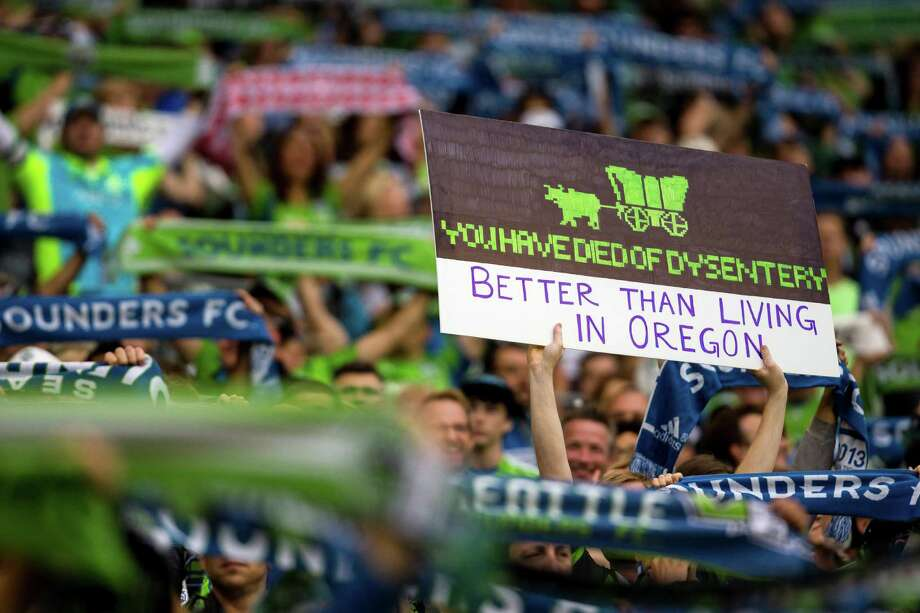 A Sounders fan shows off a creative sign referencing The Oregon Trail computer game during the first half of the Cascadia Cup match Sunday, August 25, 2013, at CenturyLink Field in Seattle. The sold-out match marked Clint Dempsey's first home game as a member of the Seattle Sounders FC. Photo: JORDAN STEAD, SEATTLEPI.COM / SEATTLEPI.COM