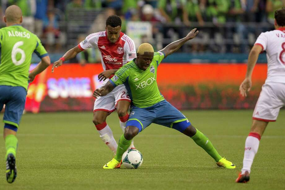 Eddie Johnson, center right, battles for ball control with Rodney Wallace, center left, during the first half of the Cascadia Cup match Sunday, August 25, 2013, at CenturyLink Field in Seattle. The sold-out match marked Clint Dempsey's first home game as a member of the Seattle Sounders FC. Photo: JORDAN STEAD, SEATTLEPI.COM / SEATTLEPI.COM