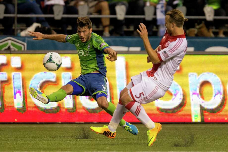 Bran Evans, left, takes a shot toward the Timbers goal from the corner of the box during the first half of the Cascadia Cup match Sunday, August 25, 2013, at CenturyLink Field in Seattle. The sold-out match marked Clint Dempsey's first home game as a member of the Seattle Sounders FC. Photo: JORDAN STEAD, SEATTLEPI.COM / SEATTLEPI.COM