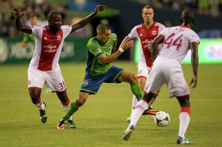 Clint Dempsey, center, weaves through Timbers defense during the first half of the Cascadia Cup match Sunday, August 25, 2013, at CenturyLink Field in Seattle. The sold-out match marked Clint Dempsey's first home game as a member of the Seattle Sounders FC. Photo: JORDAN STEAD, SEATTLEPI.COM / SEATTLEPI.COM