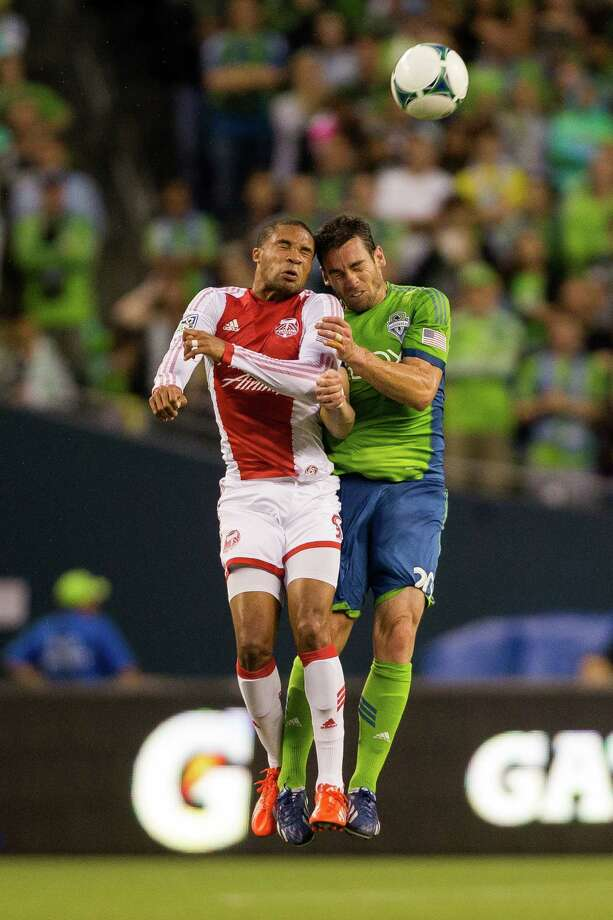Zach Scott, right, collides with a Timbers player while going up for a header during the first half of the Cascadia Cup match Sunday, August 25, 2013, at CenturyLink Field in Seattle. The sold-out match marked Clint Dempsey's first home game as a member of the Seattle Sounders FC. Photo: JORDAN STEAD, SEATTLEPI.COM / SEATTLEPI.COM