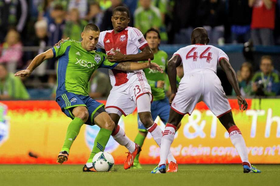 Clint Dempsey, left, pushes past Alvas Powell, center, during the second half of the Cascadia Cup match Sunday, August 25, 2013, at CenturyLink Field in Seattle. The Sounders beat the Timbers 1-0. The sold-out match marked Clint Dempsey's first home game as a member of the Seattle Sounders FC. Photo: JORDAN STEAD, SEATTLEPI.COM / SEATTLEPI.COM