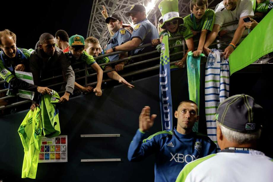 Clint Dempsey, right, leaves the field after autographing scarves for fans following the second half of the Cascadia Cup match Sunday, August 25, 2013, at CenturyLink Field in Seattle. The Sounders beat the Timbers 1-0. The sold-out match marked Clint Dempsey's first home game as a member of the Seattle Sounders FC. Photo: JORDAN STEAD, SEATTLEPI.COM / SEATTLEPI.COM
