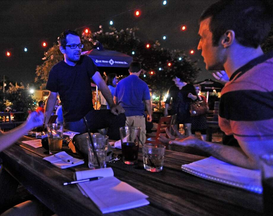 Zach Butler, left, and Kass Belaire, right, discuss a question during the Geeks Who Drink trivia game on Tuesday, July 2, 2013, at Luke's. Photo taken: Randy Edwards/The Enterprise