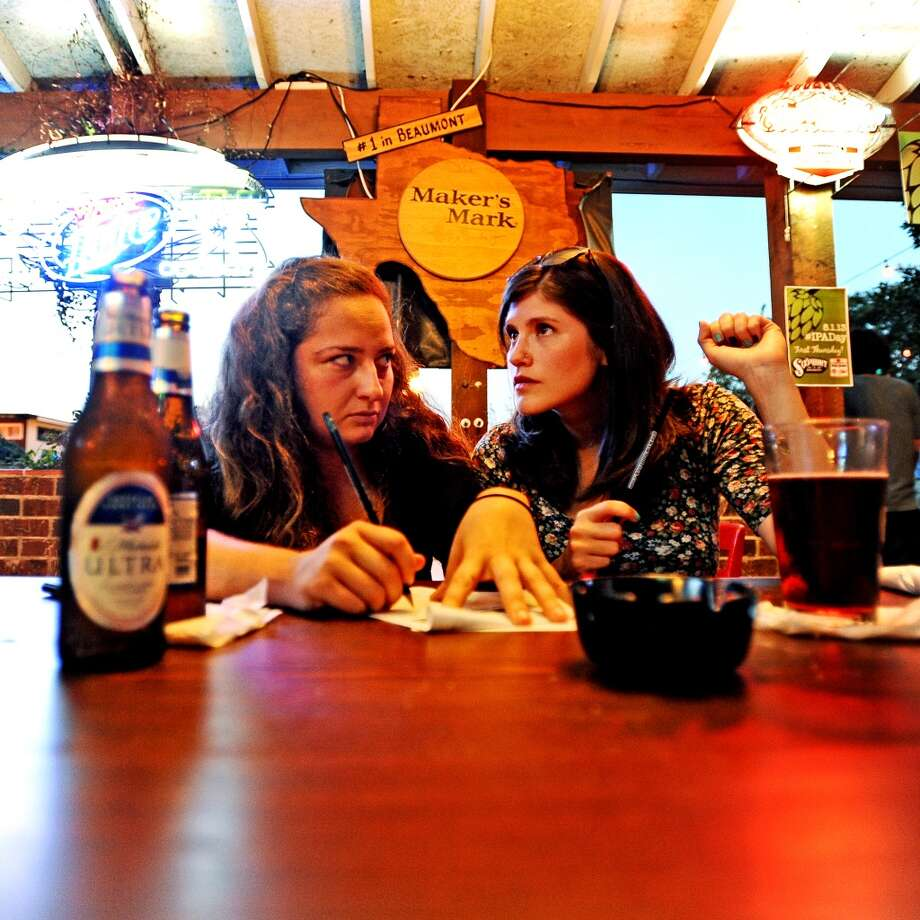 Lucy Biebel, left, and  Laura Steele, right, team up to figure out the name of a song in the second round of the Geeks Who Drink trivia game at Luke's in Beaumont on Tuesday, July 30, 2013. Photo taken: Randy Edwards/The Enterprise