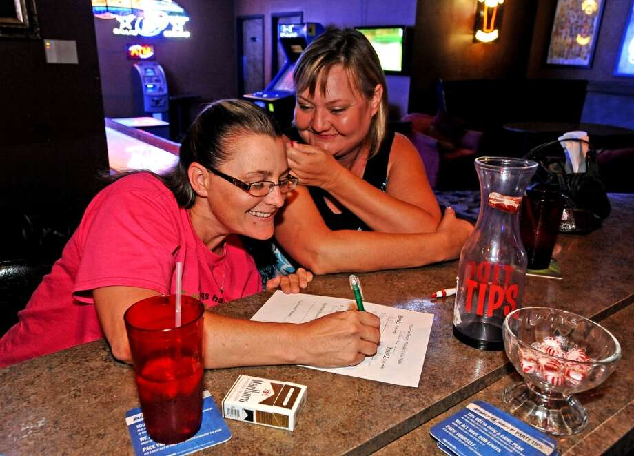 Authum MacCammond, left, and Theresa Hebert, right, whisper answers to each other during the Thirty Thursday Trivia at the PaceSetter on Thurday, Augut 1, 2013. Photo taken: Randy Edwards/The Enterprise