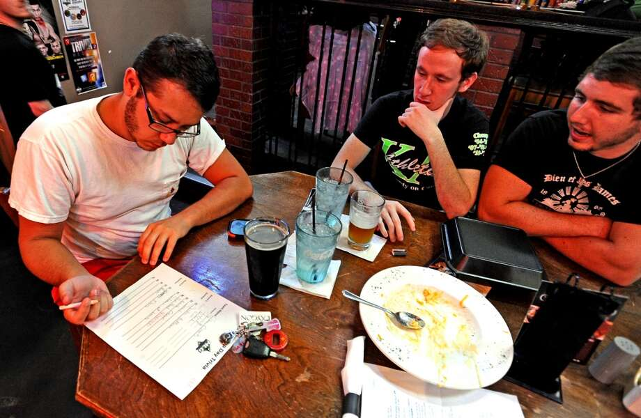 From left to right; Travis Hensley, Cody Riggs, and Dalton Locklear discuss answers during round two of Hump Day Trivia Night at Major League Grill on Wednesday, July 31, 2013. Photo taken: Randy Edwards/The Enterprise