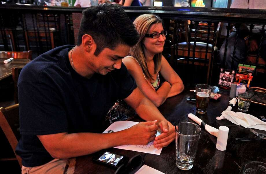 Isaac Diaz, left, covers answers from opponents across the table during round two of Hump Day Trivia Night at Major League Grill on Wednesday, July 31, 2013. Photo taken: Randy Edwards/The Enterprise