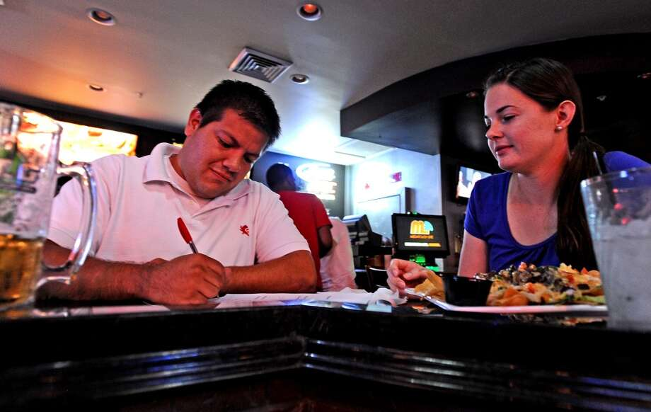 Brian and Kristine Salazar discuss answers during round two of Hump Day Trivia Night at Major League Grill on Wednesday, July 31, 2013. Photo taken: Randy Edwards/The Enterprise