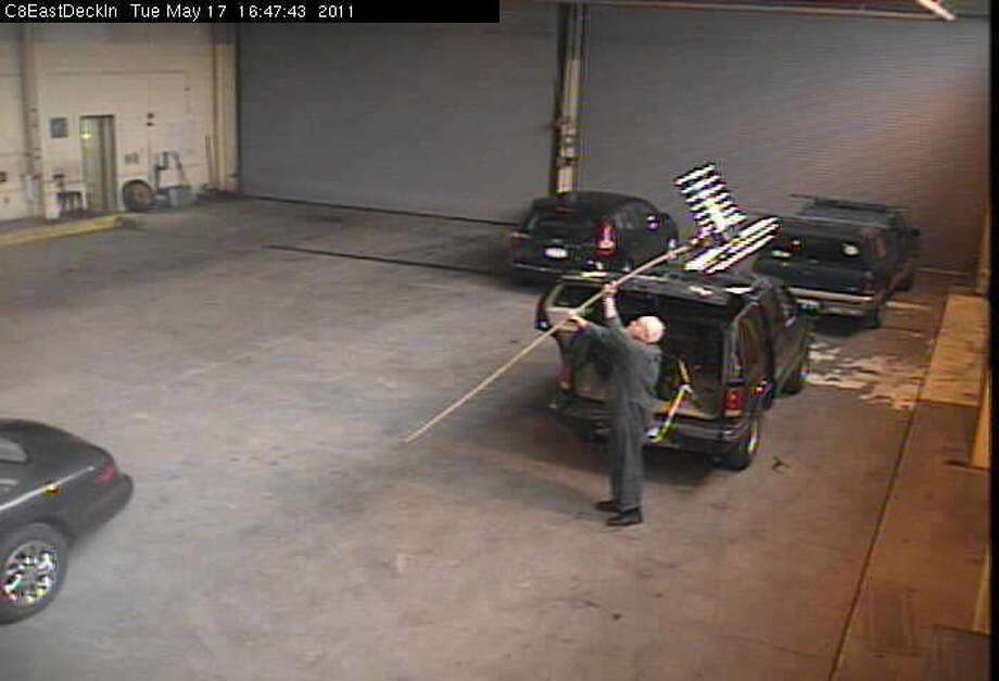 This photo from a surveillance camera shows utilities engineer Boyd        Bonner setting up an antenna near the trunk of his car        while on duty at the Sheridan Avenue Steam Plant, the state Office of        General Services says. Photo: Office Of General Services