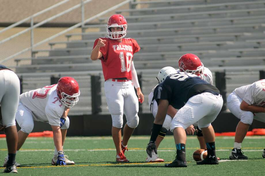 Clear Lake senior quarterback Sam Smith III, center, sets his offense, incliding lineman Evan Meyer, left, before a play during the Falcon's scrimmage versus Sam Rayburn at Clear Creek ISD Veteran's Memorial Stadium. Freelance photo by Jerry Baker Photo: Jerry Baker, For The Chronicle