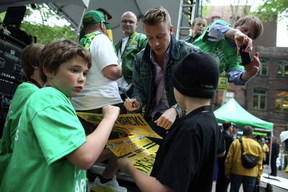 Macklemore signs autographs before he takes the stage during a rally to bring back the Seattle SuperSonics on June 14, 2012. An estimated 6,000 people packed into Occidental Park in Seattle's Pioneer Square neighborhood to show support for bringing back the team. (Joshua Trujillo, seattlepi.com) Photo: JOSHUA TRUJILLO, Seattlepi.com File Photos / SEATTLEPI.COM