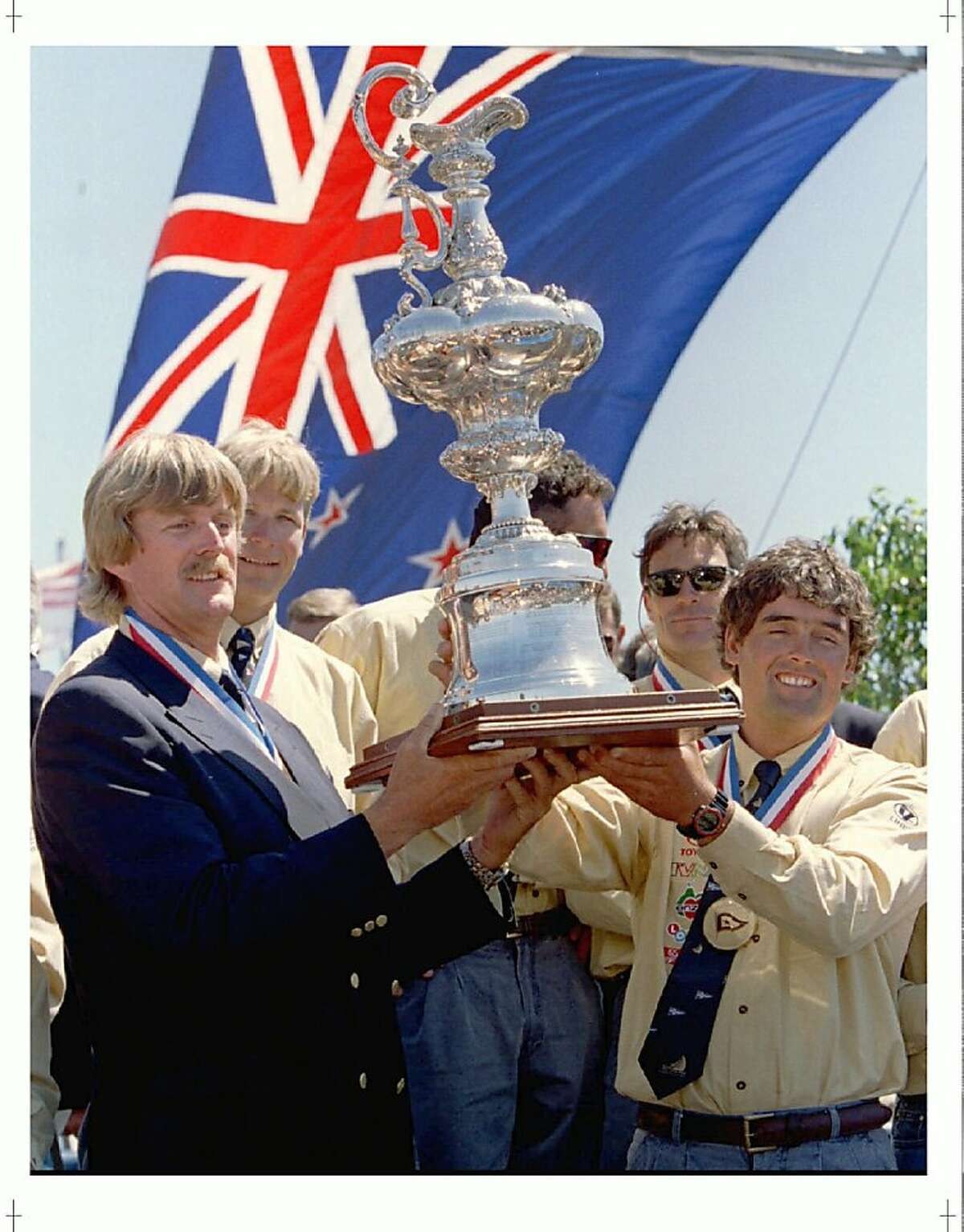 SAD02:AMERICA'S CUP:SAN DIEGO,CALIF.,15MAY95 - Team New Zealand syndicate head Peter Blake (L) and skipper Russell Coutts hold up the America's Cup before the national flag, after it was officially presented to New Zealand for safekeeping, during ceremonies in San Diego, May 15. The oldest trophy in the sporting world, the America's Cup has only been away from American soil twice in its 144-year history. bps/Photo by Blake Sell REUTERS