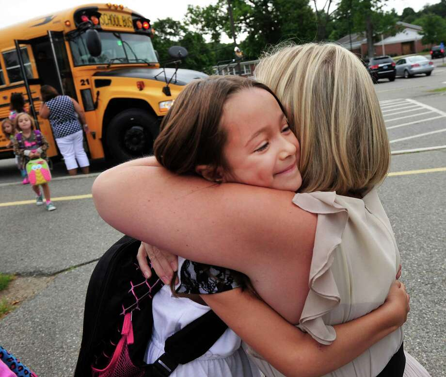 Mariela Guerrero is greeted by teacher Elisa Larson, as first-graders begin their first day of school at Center School in Brookfield, Conn. Monday, Aug. 26, 2013. Photo: Michael Duffy / The News-Times