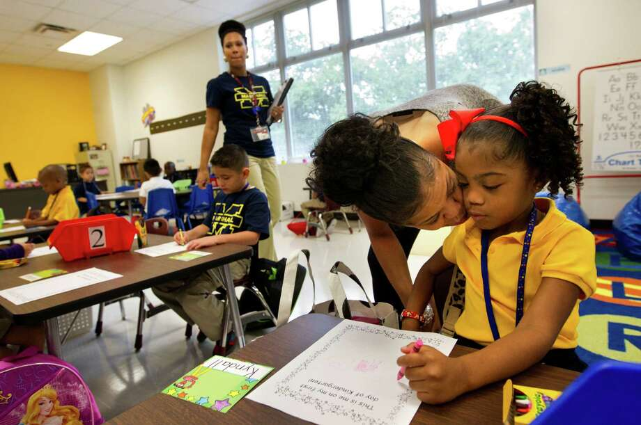 "Josie Roberts kisses her daughter, Kyndall Roberts, 5, goodbye during the first day of school at Thurgood Marshall Elementary, Monday, Aug. 26, 2013, in Houston. ""I cried last year, I'm not going to cry this year,"" Josie said. The school is a former North Forest school being absorbed by the Houston Independent School District. Photo: Cody Duty, Houston Chronicle / © 2013 Houston Chronicle"