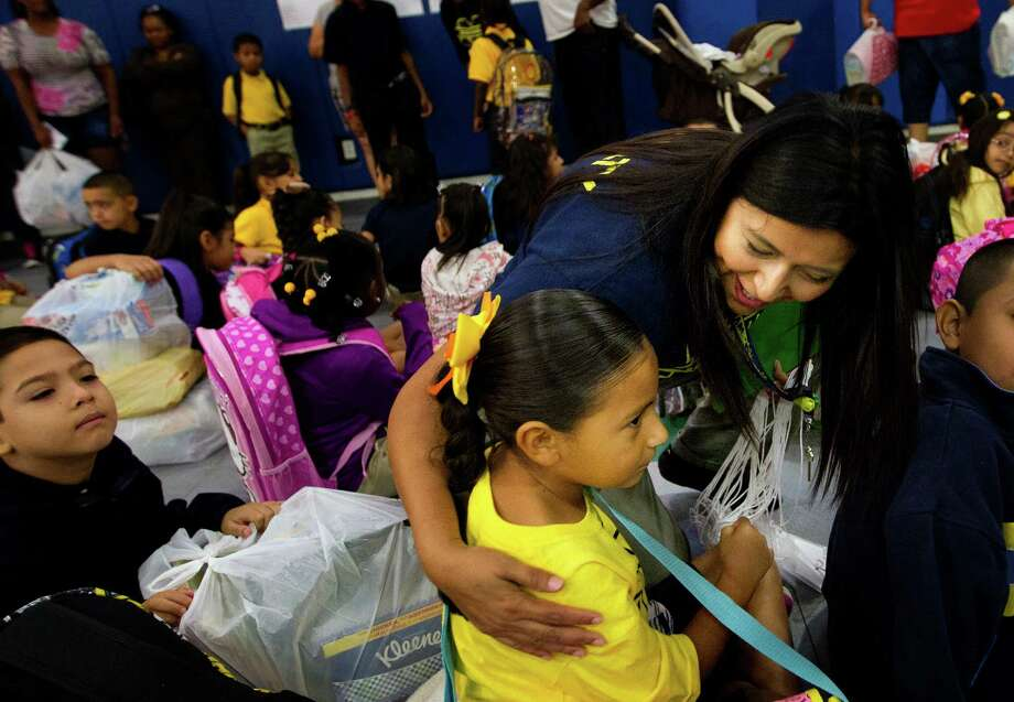 Chloe Cortez, 5, left, gets a hug from her mom, bilingual kindergarten teacher Maria Cortez, right, during the first day of school at Thurgood Marshall Elementary, Monday, Aug. 26, 2013, in Houston. The school is a former North Forest school being absorbed by the Houston Independent School District. Photo: Cody Duty, Houston Chronicle / © 2013 Houston Chronicle