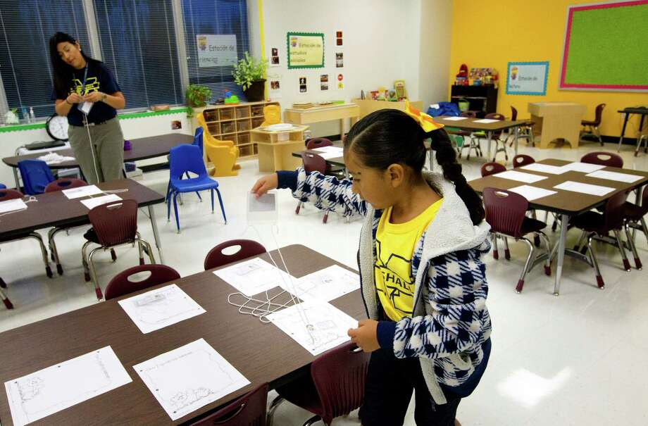 Chloe Cortez, 5, right, helps her mom, bilingual kindergarten teacher Maria Cortez, left, prepare her classroom during the first day of school at Thurgood Marshall Elementary, Monday, Aug. 26, 2013, in Houston. The school is a former North Forest school being absorbed by the Houston Independent School District. Photo: Cody Duty, Houston Chronicle / © 2013 Houston Chronicle