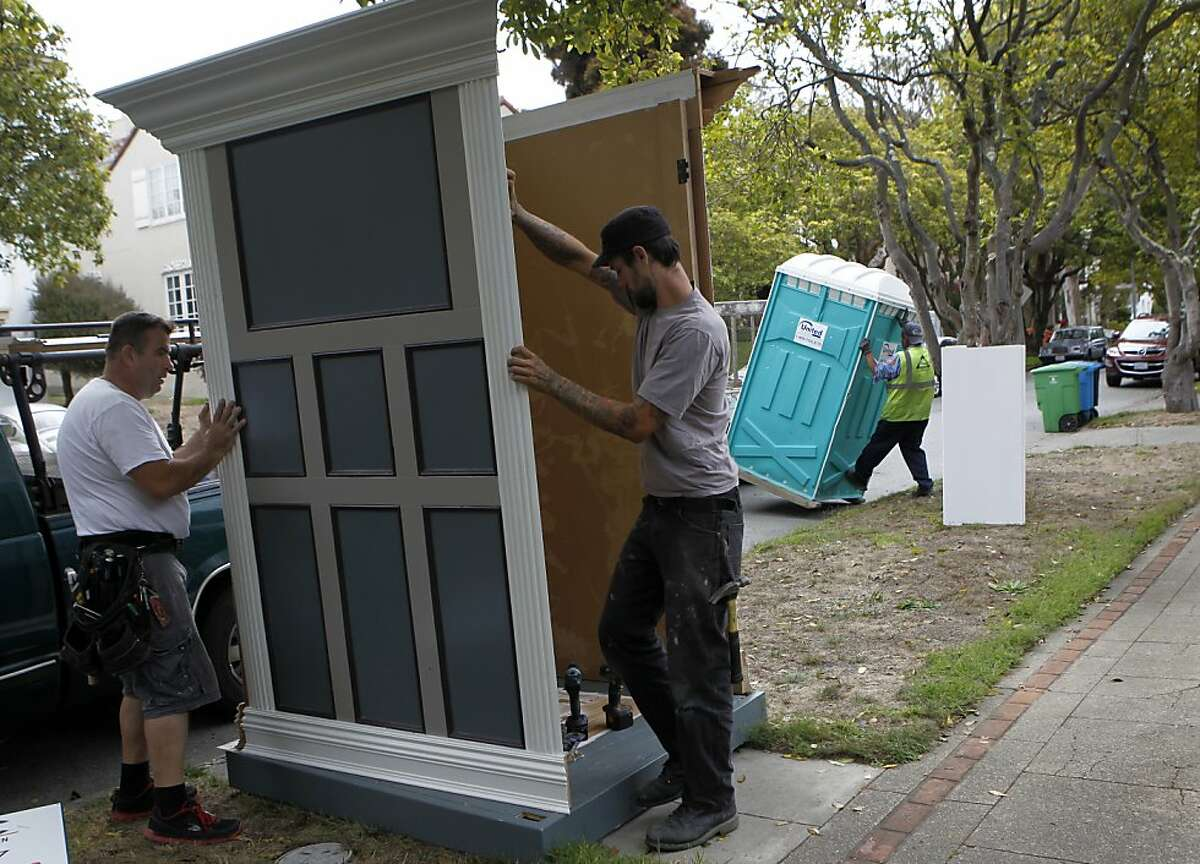 Senad Mehmdovic (left) and Dustin Olander assemble a booth to disguise porta-potty being delivered (right) at a residential work site the St. Francis Woods neighborhood of San Francisco, Calif. on Thursday, Aug. 22, 2013.