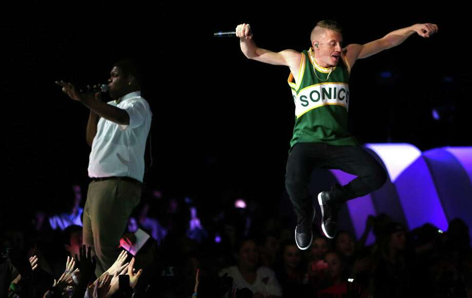 Macklemore and Ray Dalton, left, perform during We Day on Wednesday, March 27, 2013, at KeyArena in Seattle. The event brought thousands of middle and high school students together to hear from a list of celebrities and motivational speakers. We Day is a youth educational and empowerment event organized by the Free the Children charity. Students earn a seat at the event through their commitment to do good. (Joshua Trujillo, seattlepi.com) Photo: JOSHUA TRUJILLO, Seattlepi.com File Photo / SEATTLEPI.COM