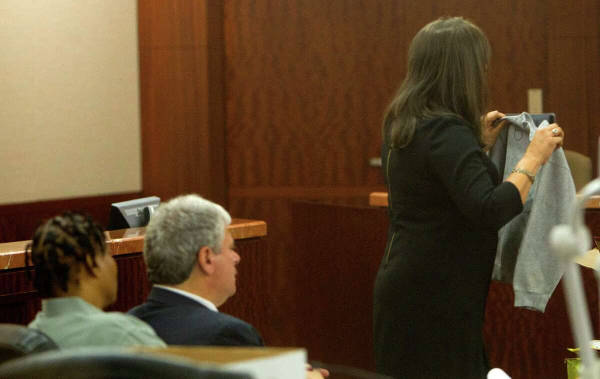 Mona Nelson, left, sits with her lawyer, Allen Tanner, center, as prosecutor Sunni Mitchell gives her closing argument during Nelson's trial at the Harris County Criminal Courthouse, Monday, Aug. 26, 2013, in Houston. Mitchell held the shirt that belonged to Foster. Nelson is on trial for the murder of 12-year-old Jonathan Foster in 2010.