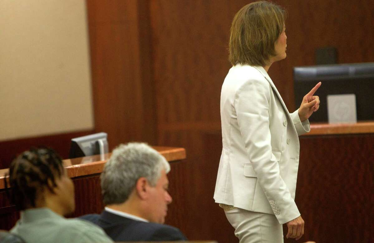 Mona Nelson, left, sits with her lawyer, Allen Tanner, center, as prosecutor Connie Spence gives her closing argument during Nelson's trial at the Harris County Criminal Courthouse, Monday, Aug. 26, 2013, in Houston. Nelson is on trial for the murder of 12-year-old Jonathan Foster in 2010.