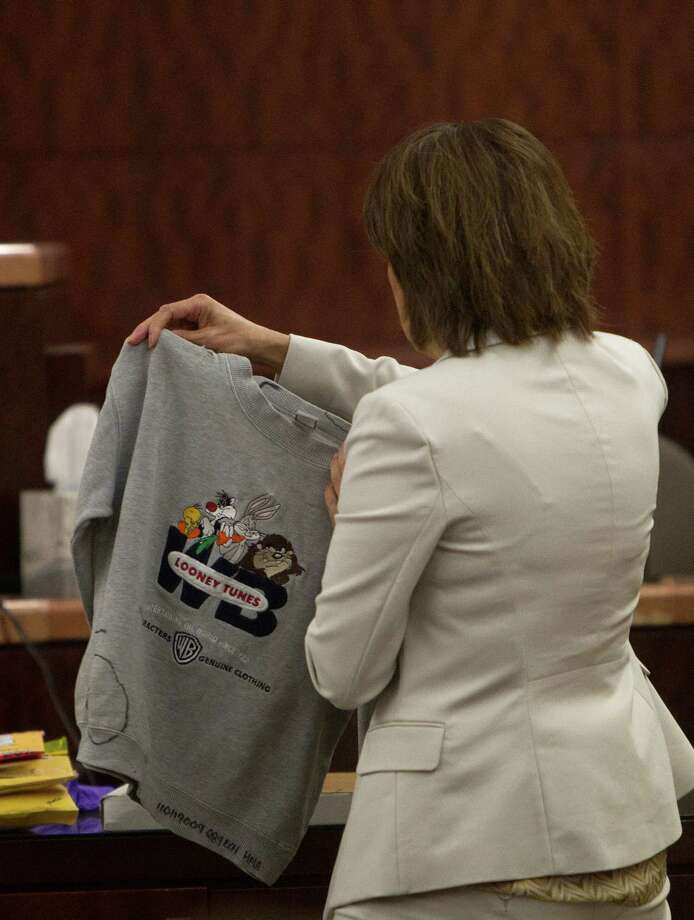 Connie Spence holds a shirt that belonged to Jonathan Foster, 12, as she gives her closing argument during Mona Nelson's capital murder trial at the Harris County Criminal Courthouse, Monday, Aug. 26, 2013, in Houston. Nelson is on trial for the murder of Foster in 2010. Photo: Cody Duty, Houston Chronicle / © 2013 Houston Chronicle