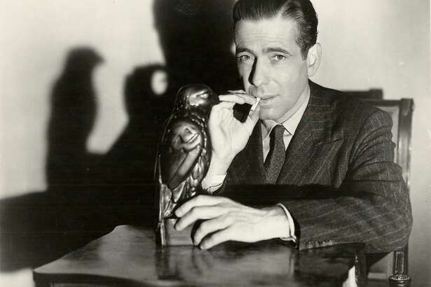 """BOGART/C/17DEC99/DD/HO-Humphrey Bogart starred in """"The Maltese Falcon."""" HANDOUT  ALSO RAN 3/13/02, 01/14/03, 12/6/03  Ran on: 02-07-2005 Humphrey Bogart, as Private Detective Sam Spade, poses with the object of desire in &quo;The Maltese Falcon.'' Ran on: 02-13-2007 Above: John Konstin, owner of John's Grill, leans disconsolately against the case the bird was taken from. Right: Humphrey Bogart, who may have dropped the statue on his toe while making the movie, in a still from the film in his role as Sam Spade. ALSO Ran on: 02-13-2007 Above: John Konstin, owner of John's Grill, leans disconsolately against the case the bird was taken from. Right: Humphrey Bogart, who may have dropped the statue on his toe while making the movie, in a still from the film in his role as Sam Spade."""
